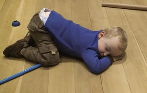 child falling asleep on cluttered floor
